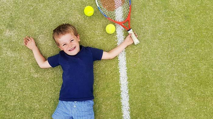 The boy lies on the tennis court and smiles
